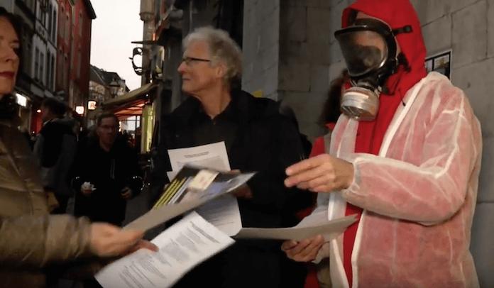"""Bürger Aachens verteilen in Atomschutzanzügen in den Straßen der belgischen Grenzstadt Flugblätter gegen """"zu wenig Katastrophen-Verhinderung"""" wegen der löchrigen Atommeiler Tiange 2 und Doel 3 (Foto: Youtube/Frontal21)"""