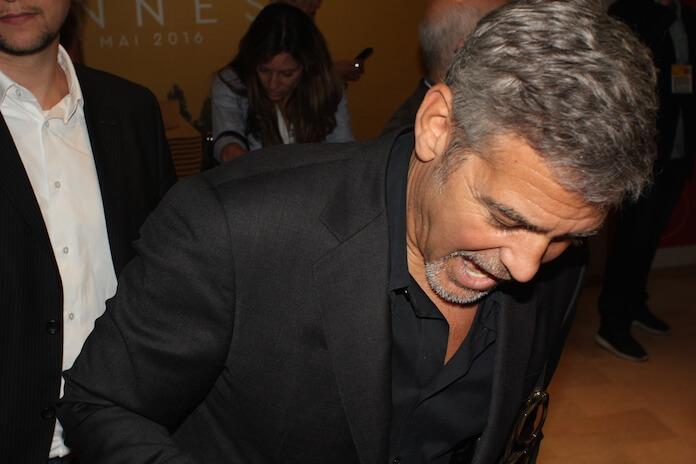 George Clooney betritt die Presse Konferenz.