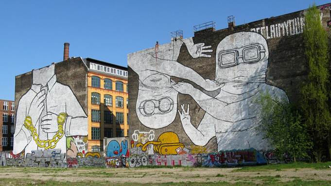 Mural created by the artist Blu depicting two men ripping each other's masks off. Source.
