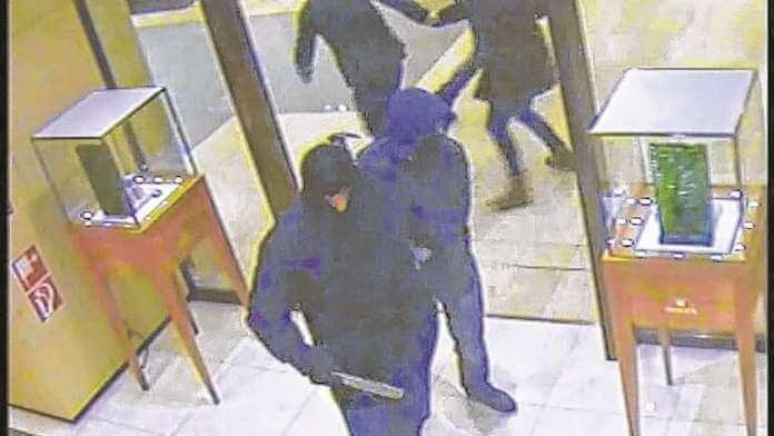 Eine Überwachungskamera des KaDeWe in Berlin-Schöneberg zeigt, wie zwei der vier Räuber vermummt mit Machete und Bauhammer zu den Vitrinen im Erdgeschoss gehen und Kunden davonrennen (Fahndungsfoto: Polizei)